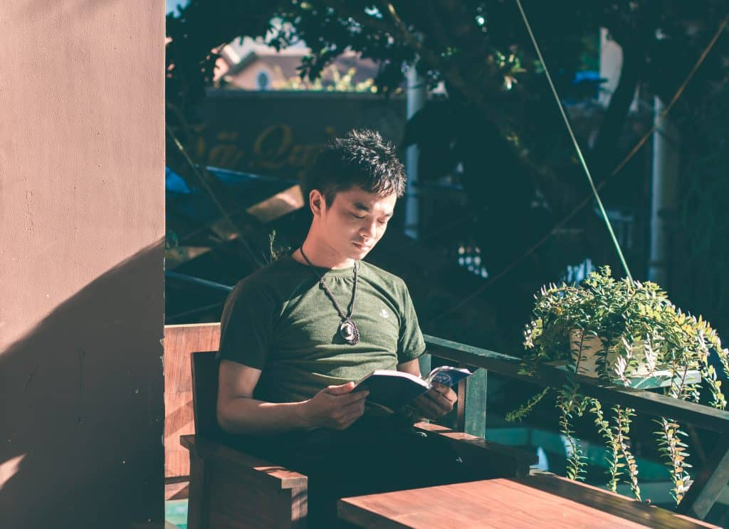 young man sitting outside reading