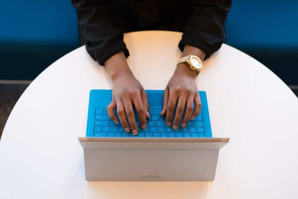 Hands typing on keyboard of a tablet