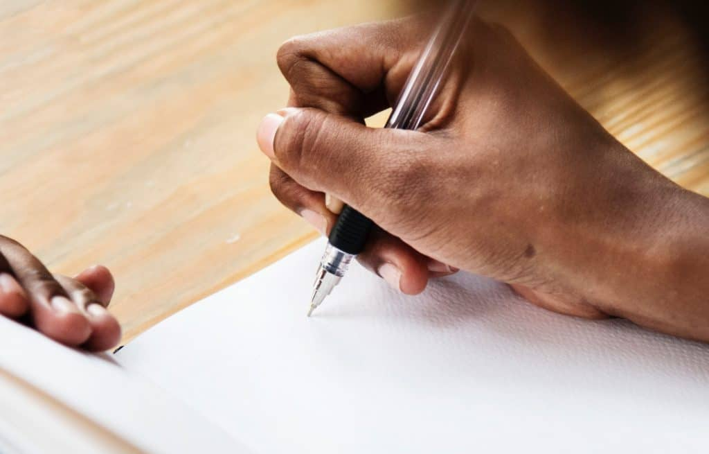hand holding pen, beginning to write on a blank page