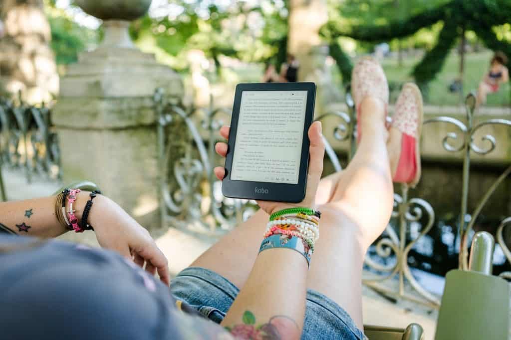 beta reader lounging outdoors reading on a tablet