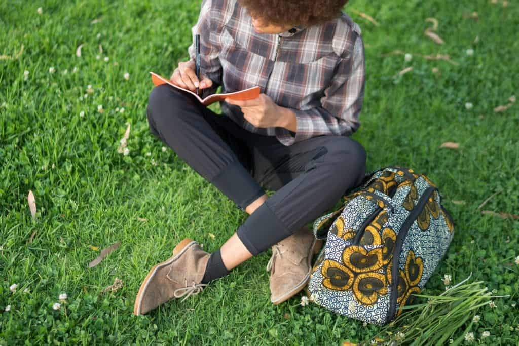 person sitting in grass writing in journal